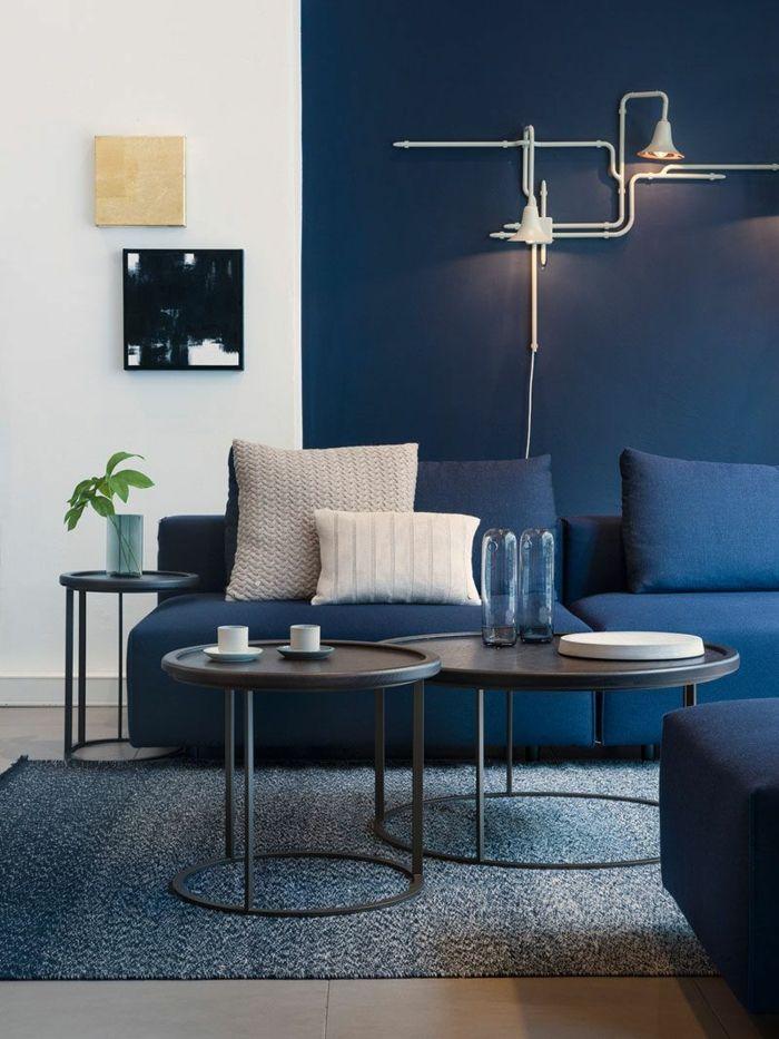 Déco Salon - mur couleur bleu foncé, sofa bleu, coussins blancs, tables basses noires, peint ...